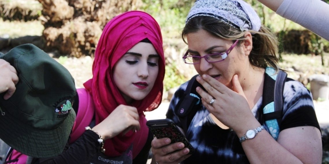 Sharing Family Photos Elicits Inter-Group Dialogue Among Arabs and Israelis